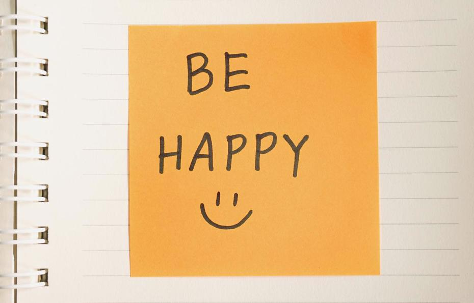 A post-it note with the words be happy and a smiley face